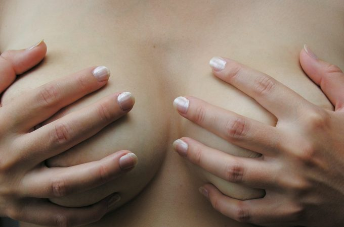 woman covering breasts with her hands