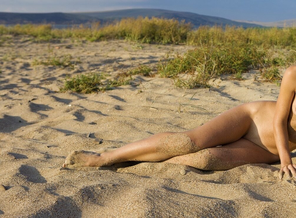 Woman laying sand at nudist beach