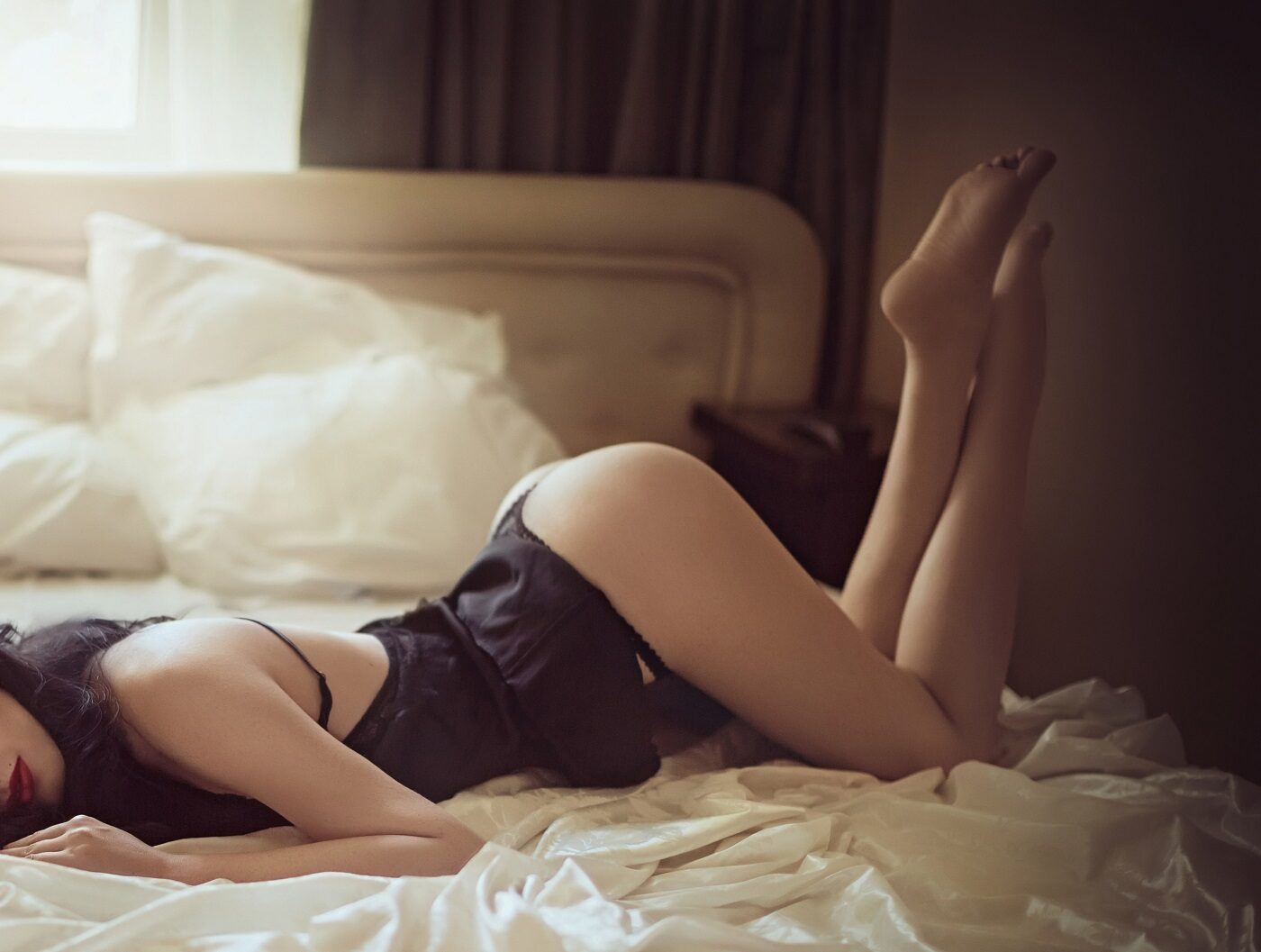 woman in black dress laying on bed