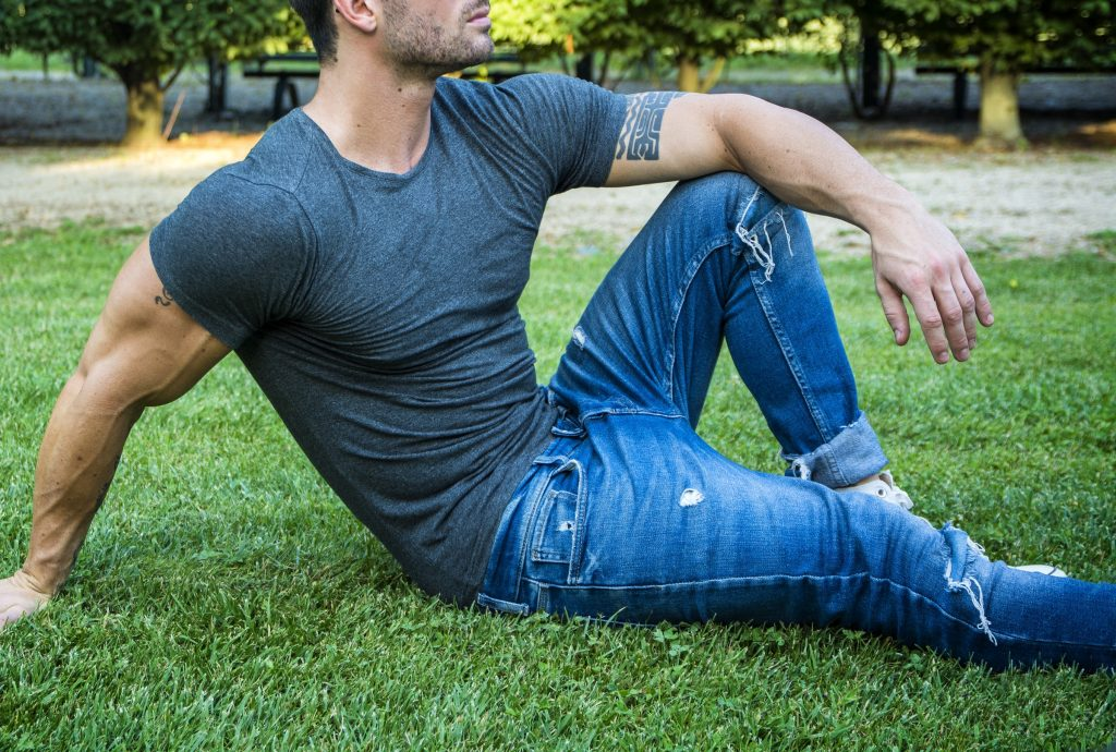 hot man sitting on grass
