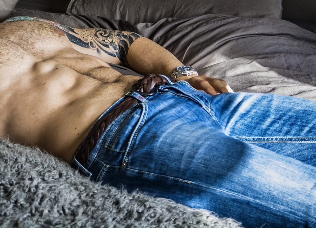 man laying on bed showing his abs