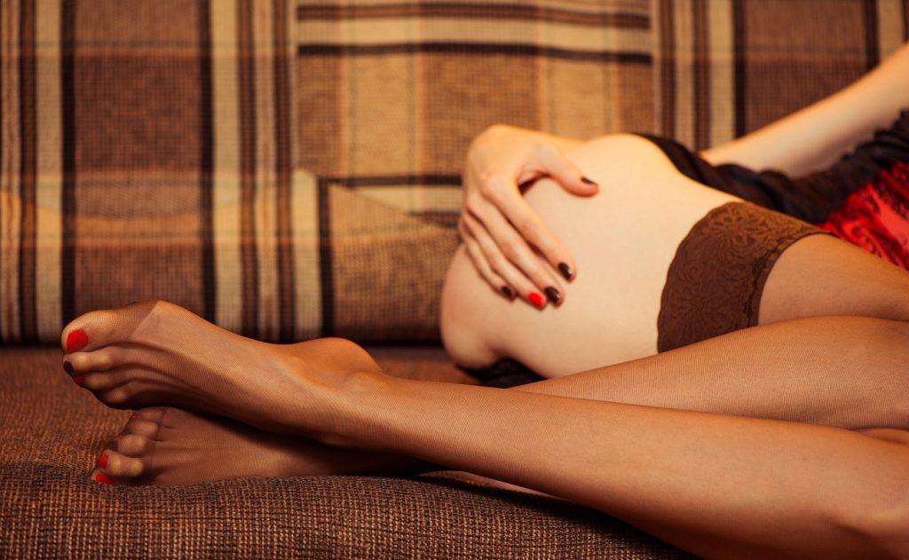 Woman in black pantyhose on sofa