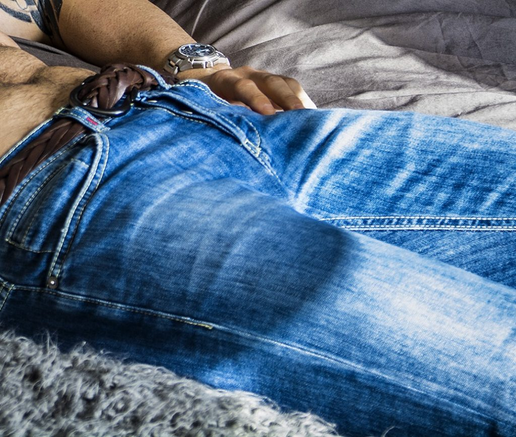 man in jeans laying on bed