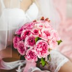 woman in bridal lingerie holding flowers
