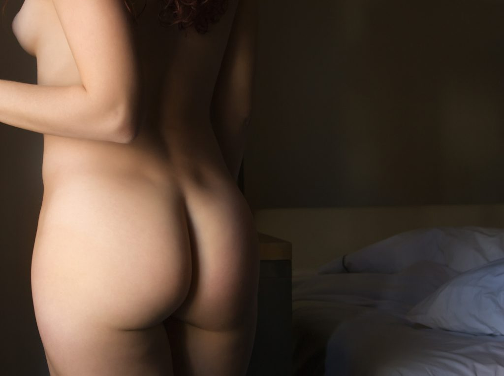 Woman standing naked in hotel