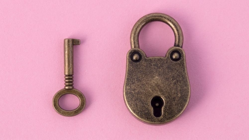 chastity lock and key on pink background